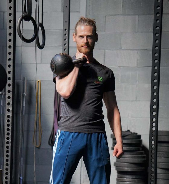 Shapelifters personal trainer Benjamin with kettlebell posing in squat rack
