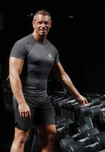 Shapelifters personal trainer Michel next to dumbbell rack